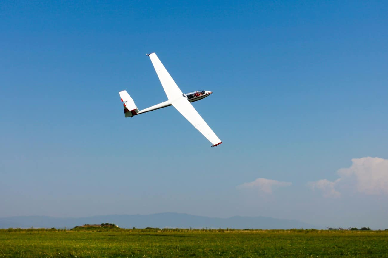 gliding plane blue skies and green grass